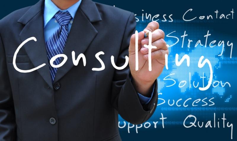Homem em pé de gravata digitando tela digital palavra consultoria em inglês